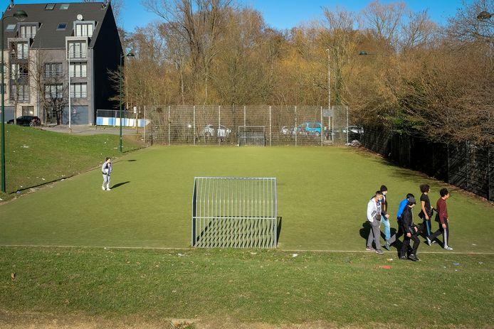 Een groepje jongeren komt chillen bij het voetbalveldje