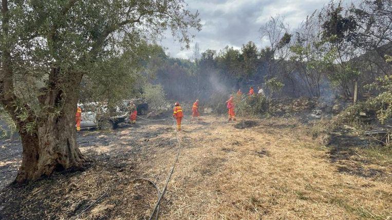 Brandweerlieden blussen een bosbrand op Sardinië. Beeld Hollandse Hoogte / EPA