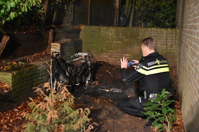 Politie bij de uitgebrande scooter in Oosterbeek.