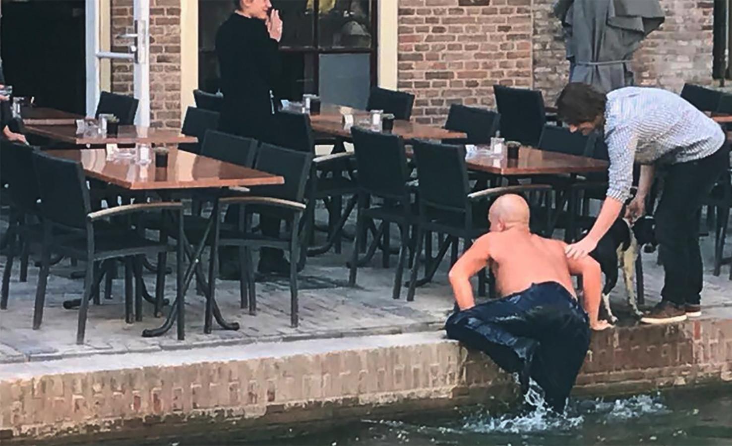 Lex klimt uit de Oudegracht nadat hij het hondje heeft gered.