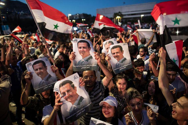 Aanhangers van de Syrische president Bashar al-Assad supporters vieren feest op het Omayyad Plein in Damascus, Syrië. Beeld AP