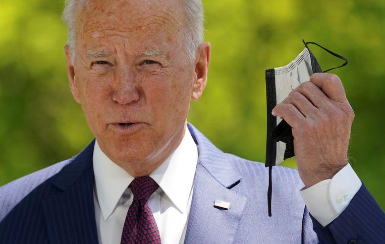 De Amerikaanse president Joe Biden doet zijn mondkapje af tijdens een aankondiging van versoepelingen in de VS. Beeld Reuters