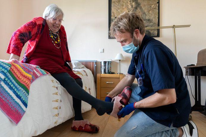 Wijkverpleegkundige Mark Verstijnen helpt Amy Seerden met haar sloffen.