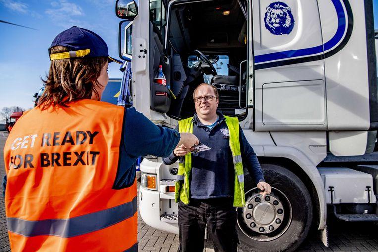 Een vrouw deelt in de haven van Rotterdam flyers uit waarin truckchauffeurs worden ingelicht over de formaliteiten na de brexit. Beeld EPA