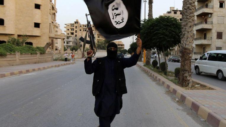 Een strijder van Islamitische Staat zwaait met een vlag van het kalifaat. Beeld null