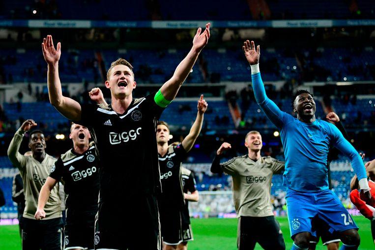 Spelers van Ajax vieren de overwinning met de meegereisde supporters in het Santiago Bernabéu-stadion. Beeld AFP