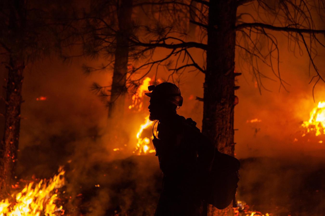 Een brandweerman tijdens nachtelijk bluswerk in Oregon.