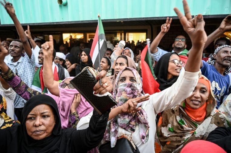 Betogers brengen het V-teken als mede-demonstranten uit de Soedanese stad Atbara per trein aankomen in Khartoem. Beeld AFP