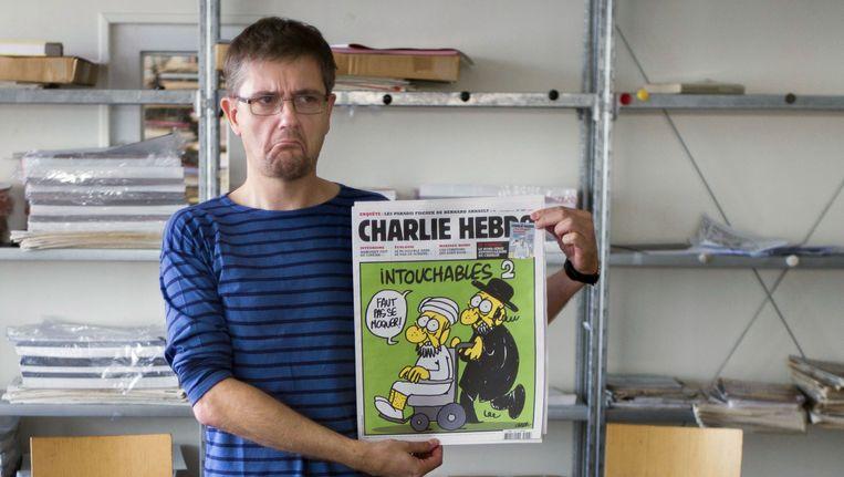 Hoofdredacteur met het in 2012 gepubliceerde nummer 'Intouchables 2' in de hand. Beeld AFP
