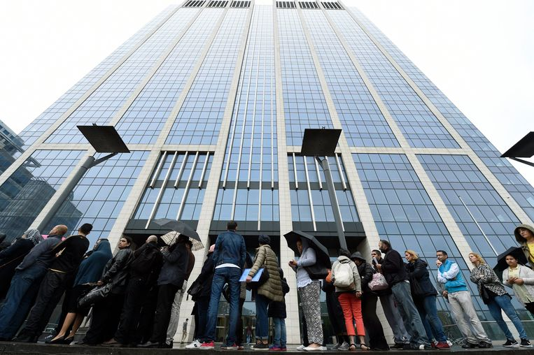Mensen staan in de rij voor de Finance Tower in Brussel op de laatste dag voor hulp met hun belastingsaangifte. Archieffoto. Beeld Photo News