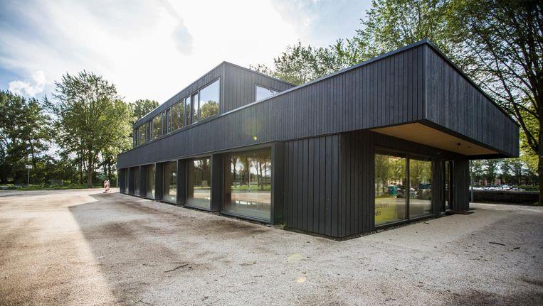 Het Van Eesteren Paviljoen met een plak asfalt rondom en een kantoordeur als entree Beeld Eva Plevier