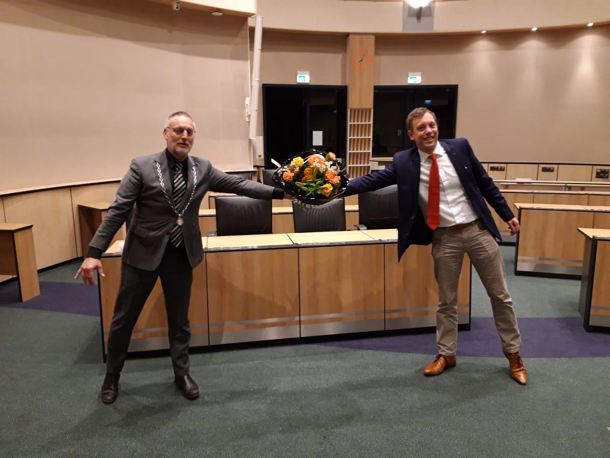 Michiel Wiersinga (r) krijgt bij zijn benoeming bloemen van burgemeester Tom Horn.