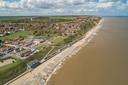 In het Britse Bacton staan huizen gevaarlijk dicht op de kliffen, waar bij stormen soms meters kust wegslaan.