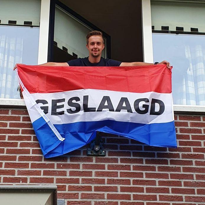 Vol trots laat Lars van Dalen de geslaagd-vlag wapperen. De scholier van het Groevenbeek uit Putten behaalde zijn vmbo tl+-diploma.