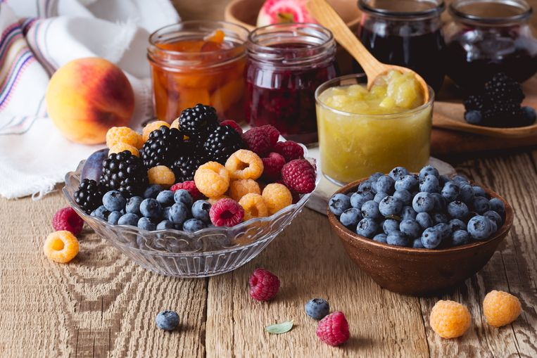 Ripe fruits and berries and assorted  of homemade jam  on  rustic wooden table. Peach, apple, rasberry, blueberry and blackberry confiture in glass jars Beeld Getty Images