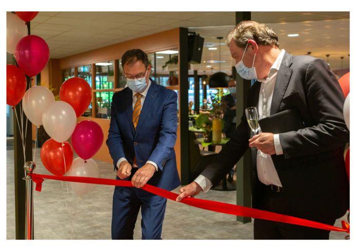 Burgemeester Van Meygaarden knipt het rode lint door bij het nieuwe spreekuurcentrum van het JBZ in LIduina in Boxtel.