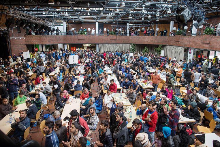 In de centrale hal van het station van Dortmund wachten honderden asielzoekers op hoe het nu verder moet. Het is een beeld uit september 2015 dat nog altijd het Duitse asielbeleid beheerst. Zelfs in het kabinet-Merkel IV zijn de verschillen groot, met Angela Merkel aan de ene kant en de minister van Binnenlandse Zaken Horst Seehofer aan de andere. Beeld EPA