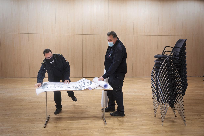 De ambtenaren Sascha Alexander Medina Azuaga (l) en Michael Gütgge buigen zich over het plan voor de inrichting van de vaccinatiestraat die in dit congrescentrum in Lemgo moet komen. Beeld Daniel Rosenthal / de Volkskrant