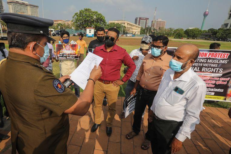 Een politieagent leest protesterende moslims in Sri Lanka de les. De regering verplicht crematies voor coronadoden, maar dat is tegen de regels van de islam. Beeld EPA
