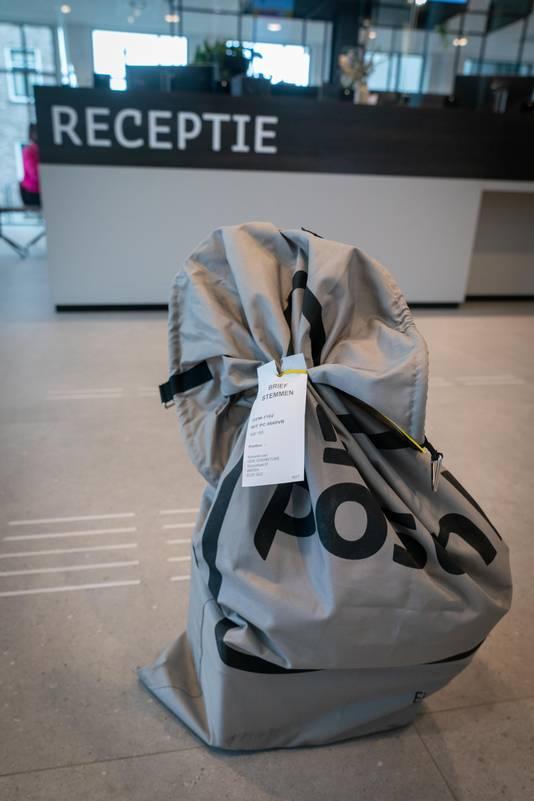 Briefstemmen voor de Tweede Kamerverkiezingen worden in zakken afgeleverd in het gemeentehuis in Overbetuwe.