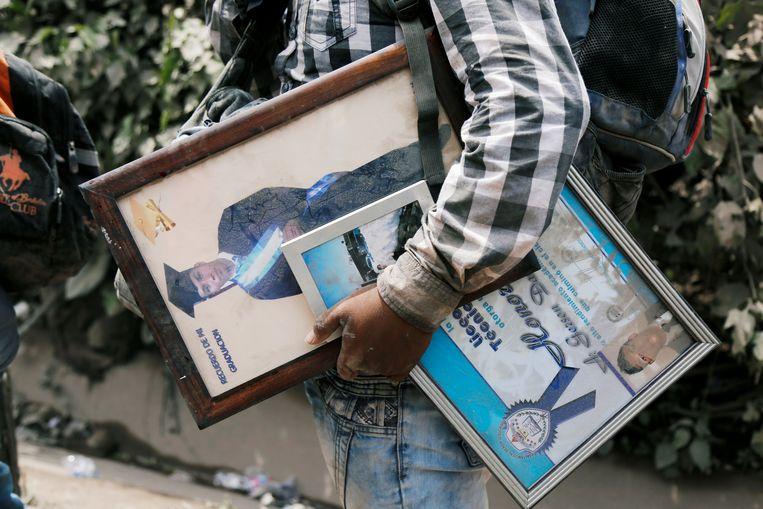 Een man redt enkele persoonlijke spullen – diploma's en foto's – in San Miguel Los Lotes in Escuintla, Guatemala, een gebied dat getroffen werd door de uitbarsting. Beeld REUTERS