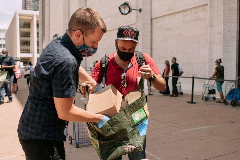 Een New Yorker ontvangt voedselhulp aan het Lincoln Center. Veel Amerikanen zijn aangewezen op liefdadigheid, want de werkloosheidsuitkering bedraagt vaak amper 150 dollar per week. Beeld AFP
