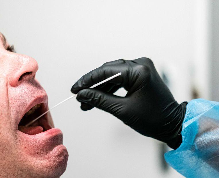 Met een wattenstaafje neemt een verpleegkundige van Medicorps wat slijm af uit de neus en mond van een personeelslid.  Beeld ANP