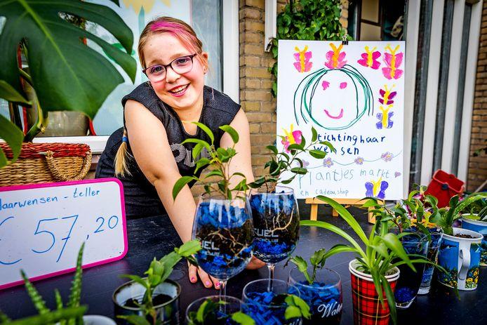Quadyra (8) met haar plantenmarkt voor haar huis aan de Heelalstraat in Dordrecht.