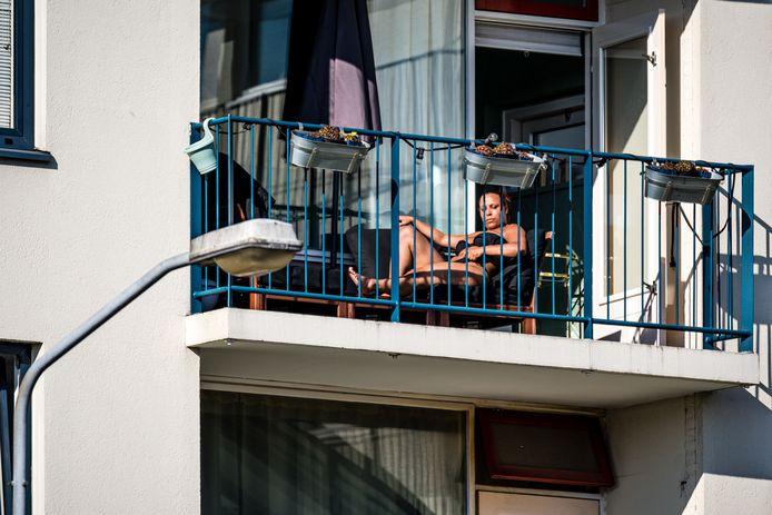 Mensen genieten thuis vanaf het balkon van het lenteweer. De overheid heeft opgeroepen publieke plaatsen te mijden, ondanks het lekkere weer.