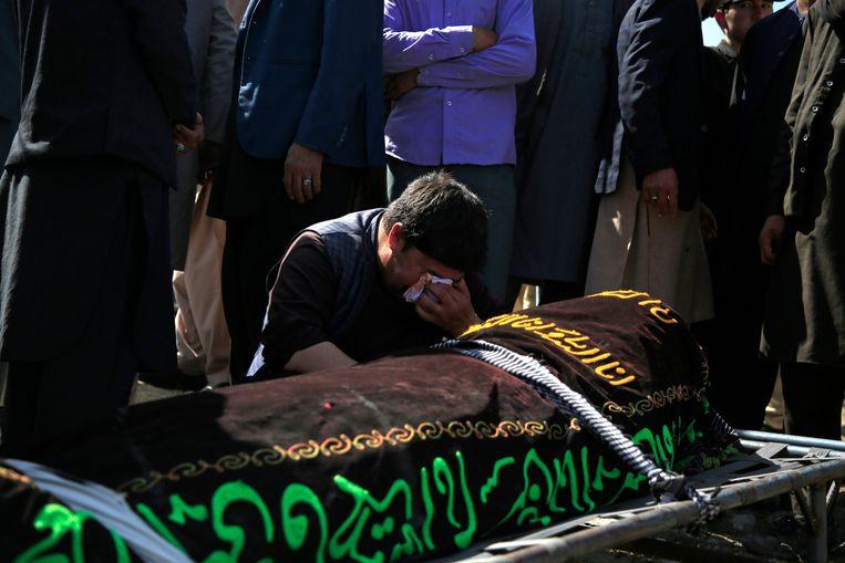 Een man rouwt bij de herdenkingsplechtigheid van een van de vele slachtoffers na de bomaanslag van 9 mei. Terroristen troffen een meisjesschool. Daarbij vielen 60 doden en meer dan 100 gewonden.  Beeld AP