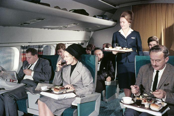 Een stewardess serveert maaltijden op een KLM-vlucht in de jaren vijftig.
