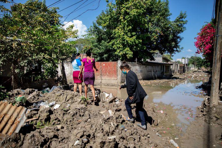 Buren Gómez, Madrid en haar dochter lopen in hun buurt over de omgewoelde modder die is achtergelaten door de orkanen Eta en Iota. Beeld Tomás Ayuso