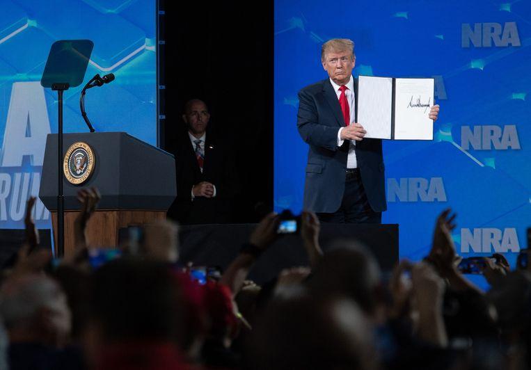 President Trump toont de handtekening waarmee hij zich uit het VN-verdrag wil terugtrekken aan leden van de National Rifle Association. Beeld AFP