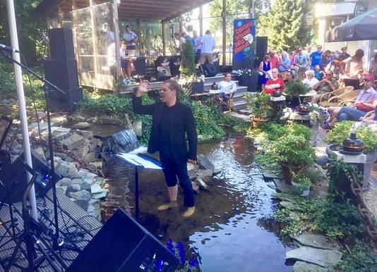 De sfeer van het Big Band festival bij Sieben op De Stok in beeld gebracht, een dirigent die niet meer op het podium past gaat spontaan in het water staan.