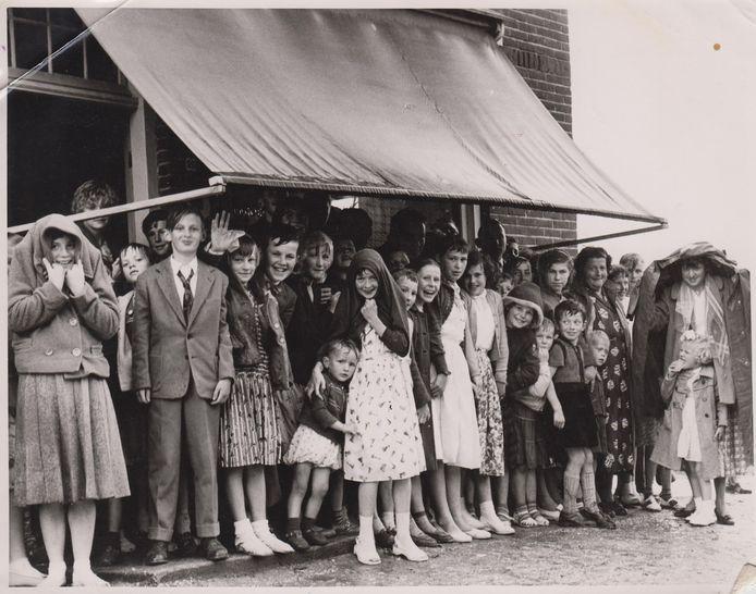 Een sportdag in Zeeland, dat staat boven deze foto. Maar geen sportkleren, wel veel regen. Zo te zien deert het de kinderen niet want ze kijken allemaal vrolijk. Wie zijn deze kinderen en paar volwassenen? En waar staan ze te schuilen voor de regen? Is het een sportdag?<br />Foto: Heemkundekring Zeeland.