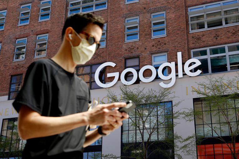 Een man kijkt op zijn mobiele telefoon voor het Google-hoofdkantoor in New York. Met advertenties bij links naar nieuwsberichten van andere media verdient Google geld. Deense media trekken nu samen op om Google te laten betalen voor het weergeven van dat nieuws. Beeld Getty Images