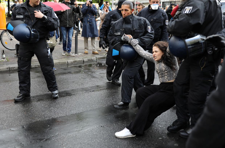 De politie arresteert een jonge vrouw op een anticoronabetoging in Berlijn. Zo'n driehonderd mensen kwamen protesteren.  Beeld REUTERS