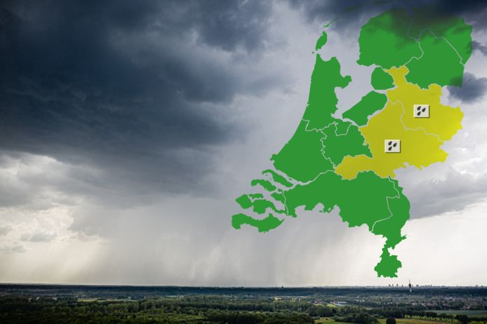 Ter illustratie. Dreigende regenwolken met kaart van Nederland waarin voor de provincies Gelderland en Overijssel code geel is afgegeven in verband met neerslag.