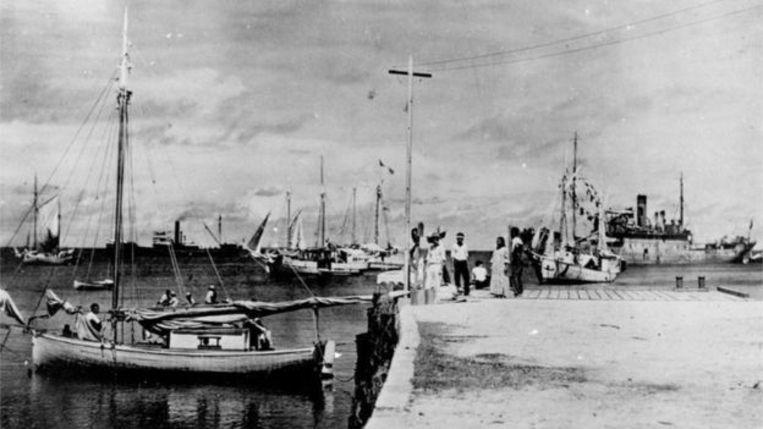 Volgens sommigen zou Amelia Earheart op de kaai zitten, met haar rug naar de camera. Links van haar zou Fred Noonan staan, en helemaal rechts in beeld haar vliegtuig. Beeld National Archives