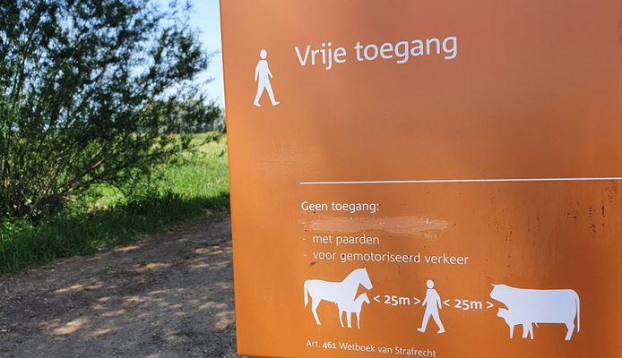 Weggekraste tekst op een bord van Staatsbosbeheer in de uiterwaarden bij Druten.