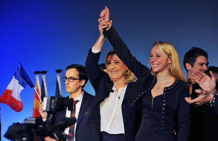 Marine Le Pen en Marion Maréchal-Le Pen laten zich het applaus van FN-aanhangers welgevallen. Beeld PHOTO_NEWS