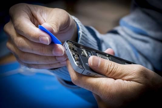 Een reparateur checkt een smartphone