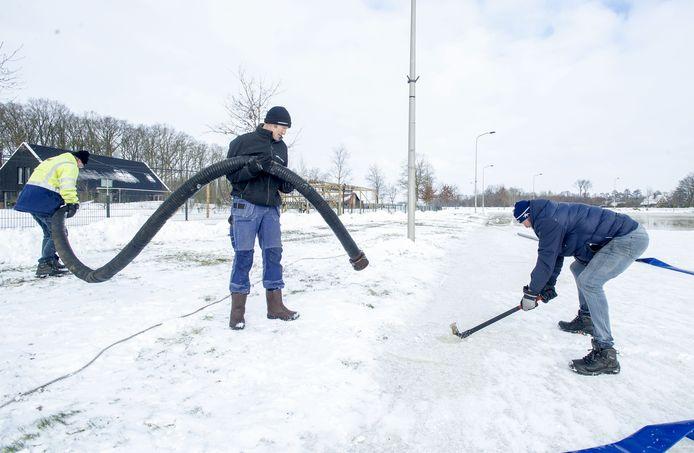 De ijsmeesters Ferdy Lohuis, Paul Meijer en Othmar Assink (van linksaf) aan het werk op de baan in Albergen.