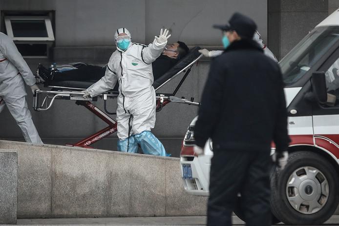 Verplegers begeleiden een patiënt bij binnenkomst in het ziekenhuis Jin Yintan in Wuhan. Volgens de Chinese overheid zouden er nu bijna 50 gevallen van besmetting zijn. (Foto Getty Images)