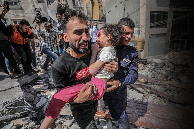 Een Palestijnse vader draagt zijn gewonde dochter weg uit een ingestort gebouw in Gaza-Stad. Dertien Palestijnen kwamen gisteren bij een Israëlische luchtaanval om het leven, meer dan veertig mensen raakten gewond. In totaal lieten sinds 10 mei al zeker 197 Palestijnen het leven, onder wie 58 kinderen, en raakten meer dan 1.200 mensen gewond. Aan Israëlische zijde vielen binnen diezelfde tijdspanne bij Palestijnse raketaanvallen vanuit Gaza tien doden, onder wie ook een kind, en 282 gewonden.  Beeld EPA