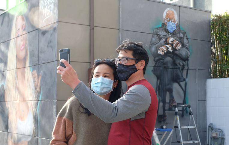 Mensen nemen een selfie voor een muurschildering van Sanders mét wanten.  Beeld AFP