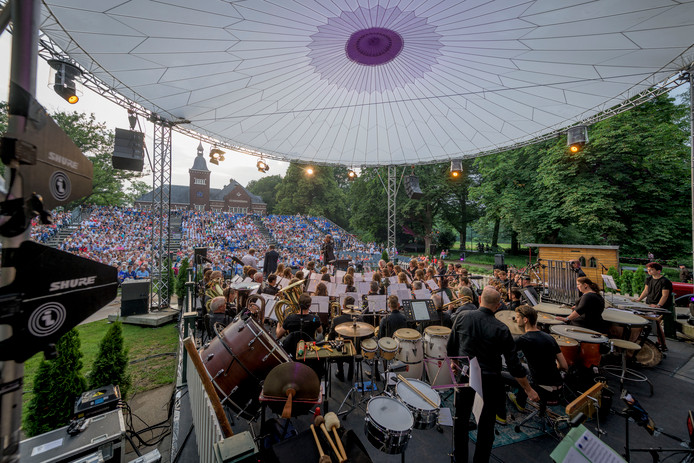 De Wilhelmina-muzikanten op het podium van de muziekkoepel in het Volkspark bij 'Rijssen Zet De Toon',  met op de achtergrond het publiek op de speciaal gebouwde tribunes en het Parkgebouw met toren.
