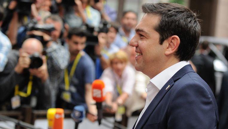 Er kan nog een lachje af bij de Griekse premier Tsipras, hoewel hem bepaald geen rustige avond wacht. Beeld EPA