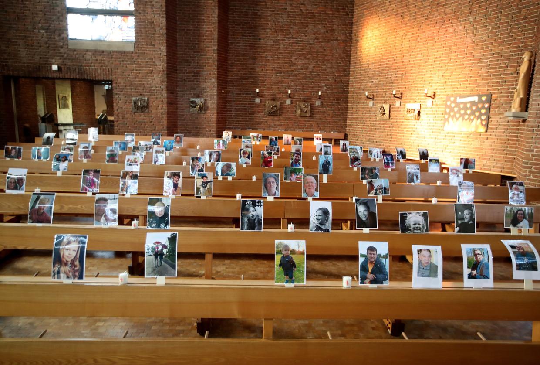 De Sint Barbarakerk in Oberhausen zit tijdens een onlineviering vol, met foto's van virtuele kerkgangers. Beeld EPA