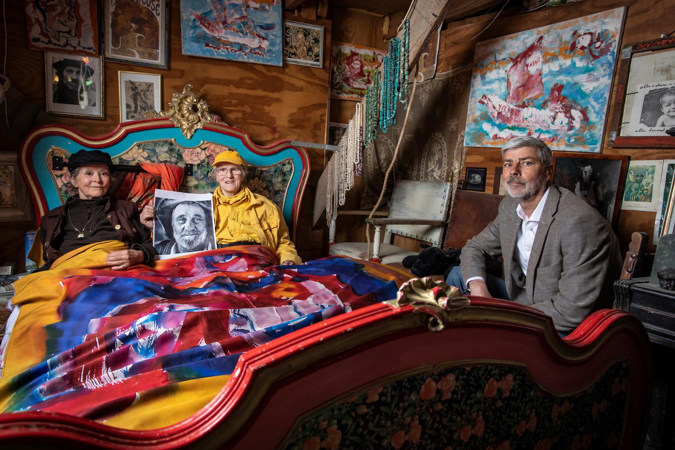 Ewald Poorthuis, directeur Twentse Damast, aan de rand van het bed met Joke (in het geel) en Lotti, twee van de 'bruiden' van wijlen Anton Heyboer. Ze liggen onder het dekbedovertrek met afdruk van Hyboers schilderij 'De Danseres.'